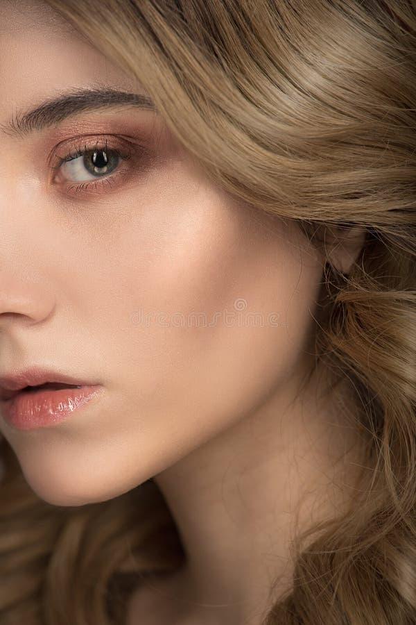 Fashion woman face closeup. Brilliance wavy hair and makeup. Light golden brown stock photography