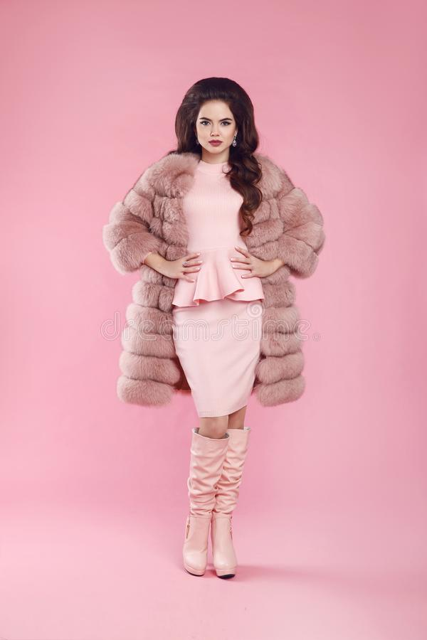 Fashion woman in fur coat and leather high boots, lady portrait stock photo