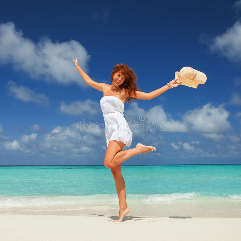 Fashion woman jumping on the beach. Happy island lifestyle. White sand, blue cloudy sky and crystal sea of tropical beach. stock photography