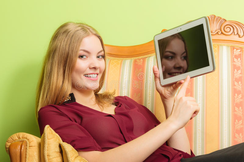 Fashion woman laying on sofa with pc tablet. royalty free stock photography
