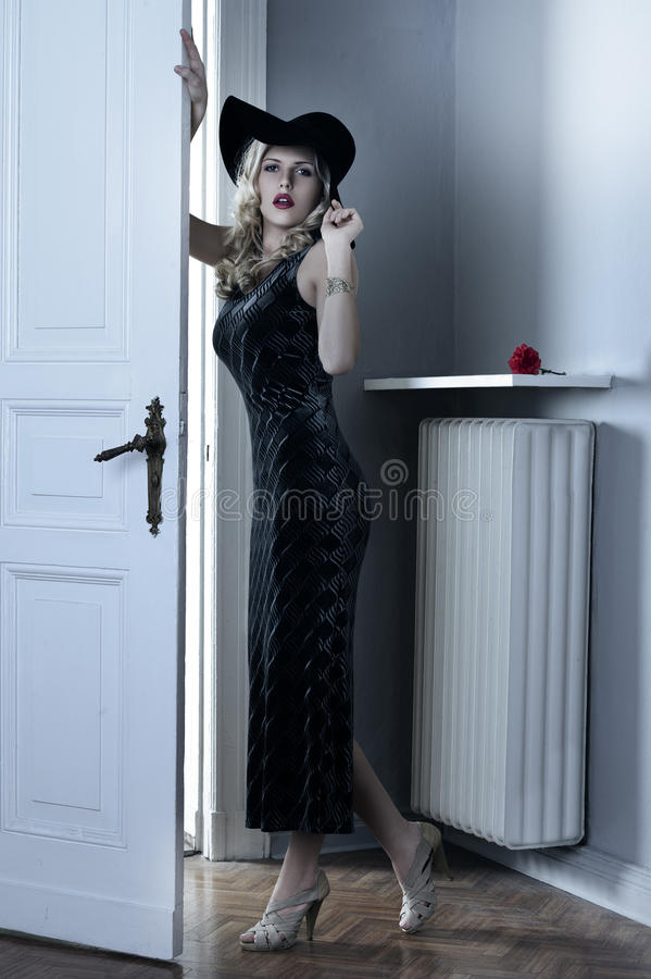 Fashion woman with long black dress and hat royalty free stock images