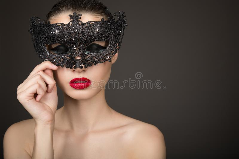 Fashion woman with long hair and red lipstick with a black mask. Dark background. Carnival, holiday royalty free stock photography