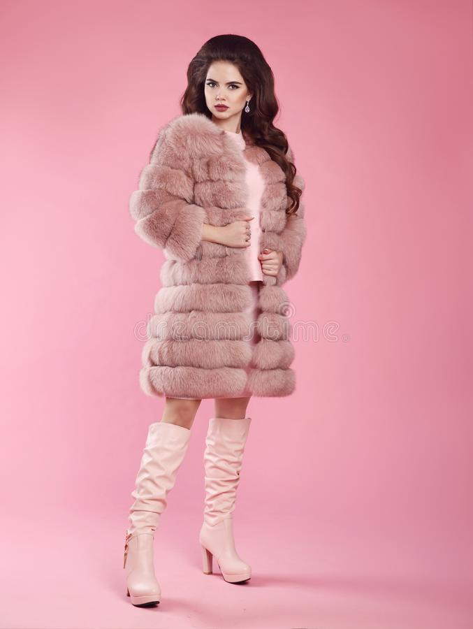 Fashion woman look. Brunette lady in fur coat and leather high b stock image
