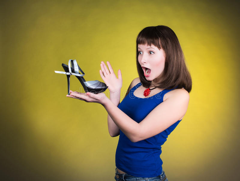 Fashion woman looking at high-heel shoe. Women love shoes concept. Screaming girl and high heels shoes on yellow background. stock photos