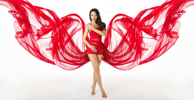 Fashion Woman Model Posing in Red Dress, Cloth Wings. Fashion Woman Model Posing in Red Dress . Flying waving Cloth as wings. Fabric Over white background stock photo