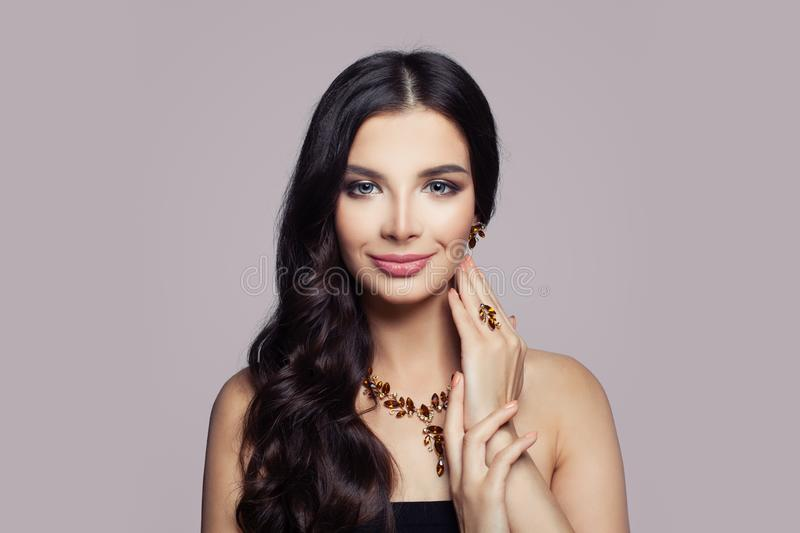 Fashion woman portrait. Girl with gold necklace, ring and earrings with amber on pink stock image