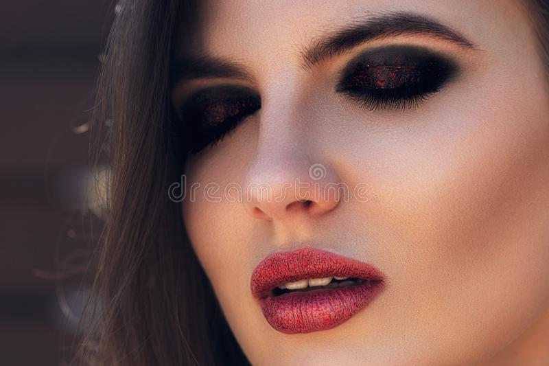 Fashion woman portrait. Sensual red shiny lips. girl model with evening makeup. Romantic hairstyle. Smoky eyes makeup. Big. Eyelashes and dark eyebrows. Perfect stock images