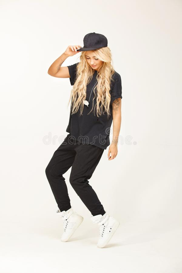 Fashion woman portrait wearing stylish swag look of black garment on white . royalty free stock image