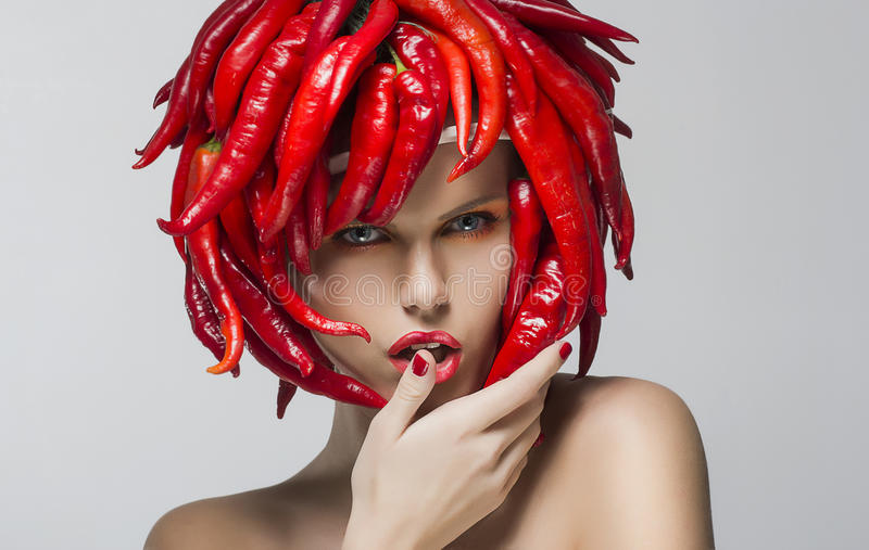 Fashion woman with red chili pepper as a headwear royalty free stock photos