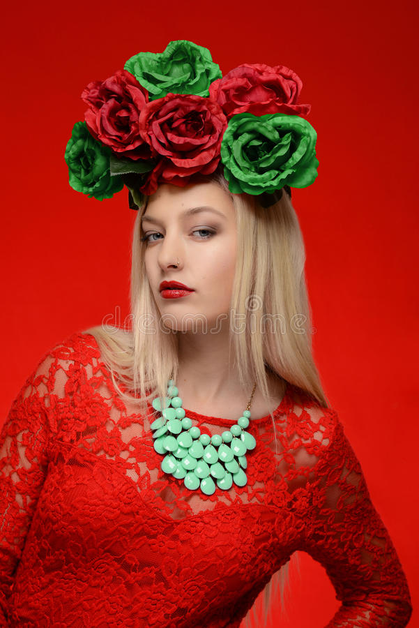 Fashion woman in red dress and flower head wreath royalty free stock photography