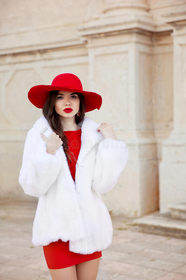 Fashion woman in red hat and dress wearing white fur coat. Elega. Nt lady. Beautiful brunette girl model in luxurious clothes posing on street. Outdoor closeup stock photo