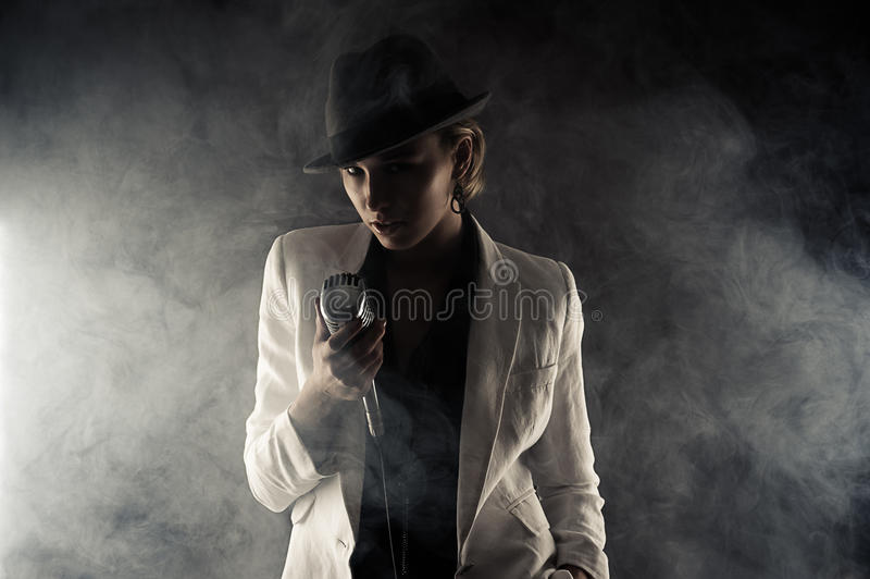 Fashion woman with retro microphone in smoke. On black background stock image