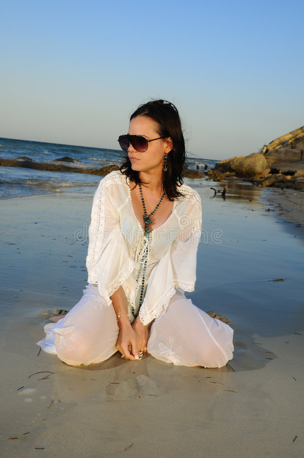 Fashion woman on the sand. Portrait of young fashion woman sitting on the sand of tropical beach royalty free stock photo