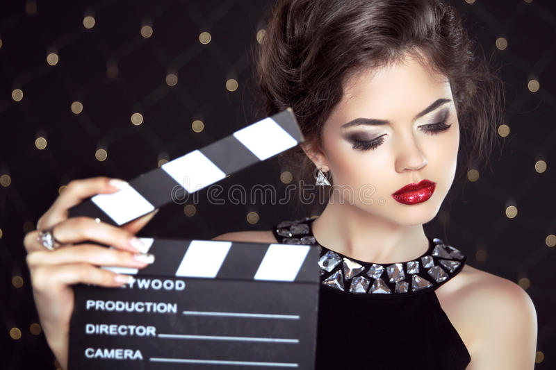 Fashion woman with red lips holding cinema clap. Super star. Model shot royalty free stock photo