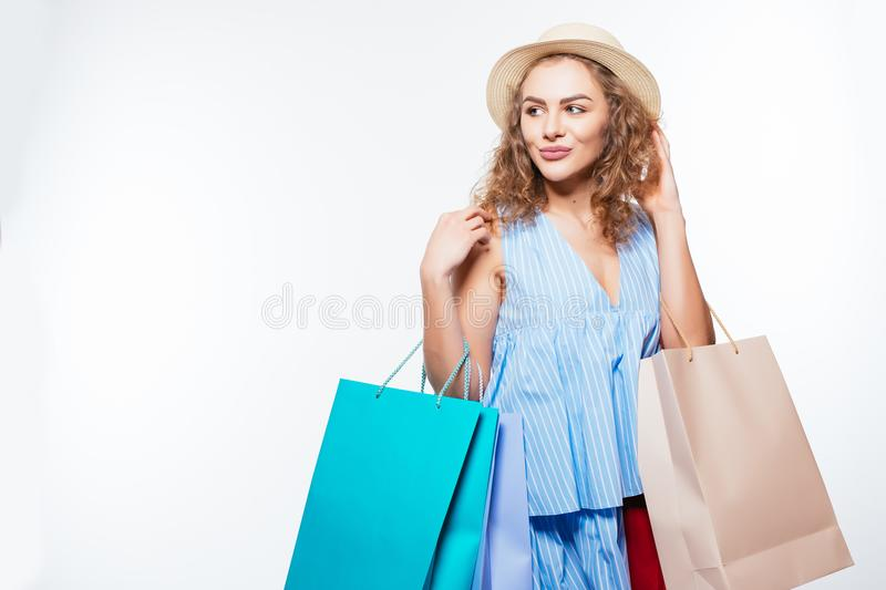 Fashion woman in summer hat with shopping bags isolated on white background royalty free stock image