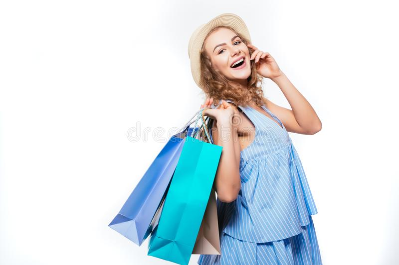 Fashion woman in summer hat with shopping bags isolated on white background royalty free stock images