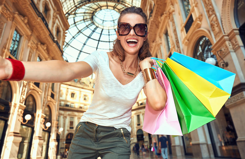 Fashion woman with shopping bags taking selfie in Galleria. Discover most unexpected trends in Milan. Smiling fashion woman in eyeglasses with colorful shopping stock images