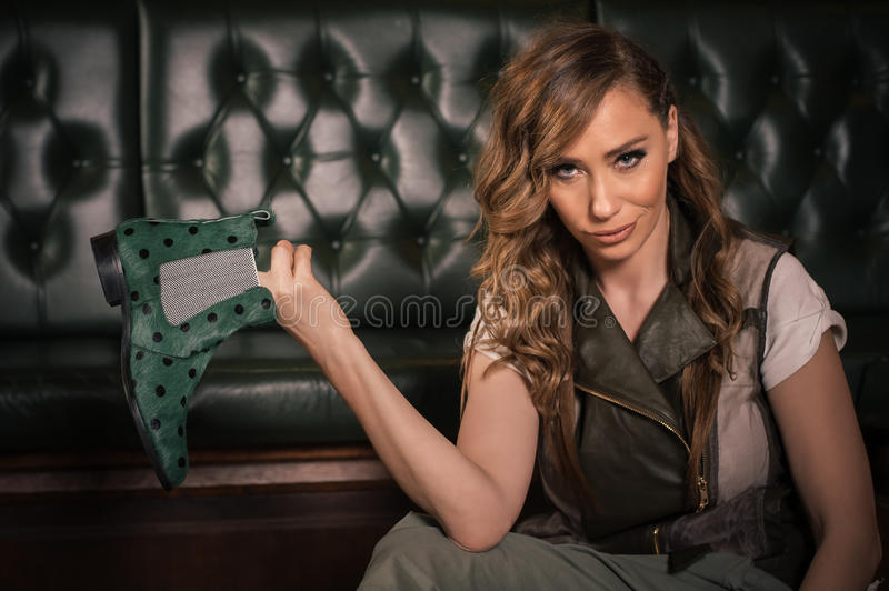 Fashion woman sitting on the floor and enjoying in shoes royalty free stock images