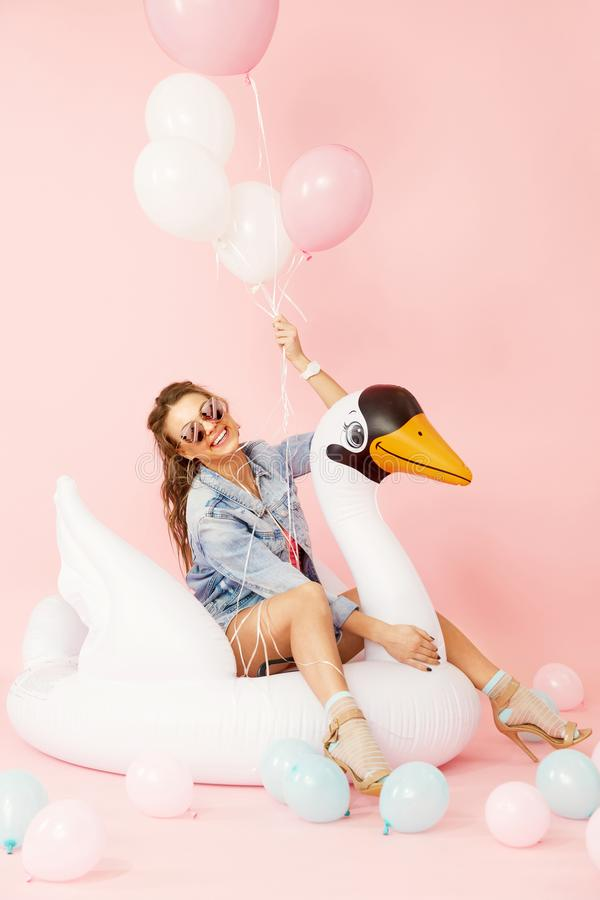 Fashion Woman In Summer Clothes Having Fun With Balloons. Happy Smiling Girl In Fashion Clothes And Stylish Sunglasses With Colorful Balloons Sitting On White stock images