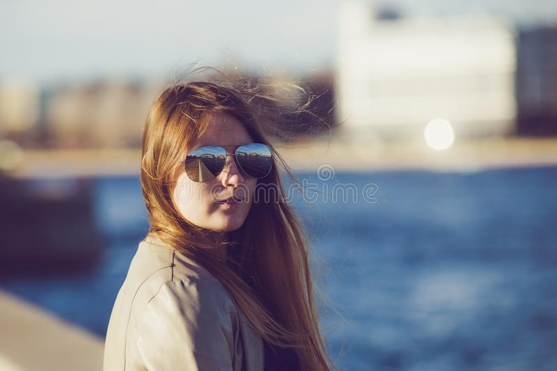 Fashion woman in sunglasses on the river embankment. outdoor portrait of young beautiful girl. Happy young smile woman sunlight ci stock photo