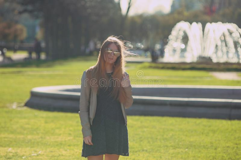 Fashion woman in sunglasses on the river embankment. outdoor portrait of young beautiful girl. Happy young smile woman sunlight ci royalty free stock photos