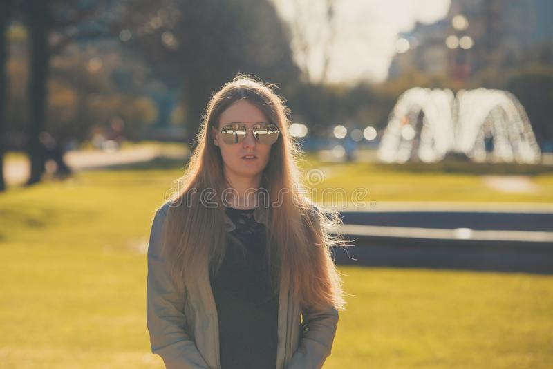 Fashion woman in sunglasses in the summer park. outdoor portrait of young beautiful girl. Happy young smile woman sunlight city po stock images