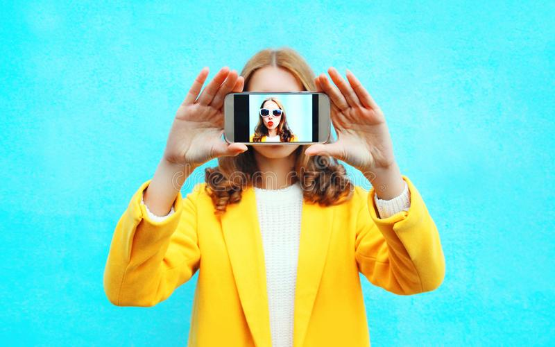 Fashion woman takes picture self portrait on smartphone on a blue. Background stock photography