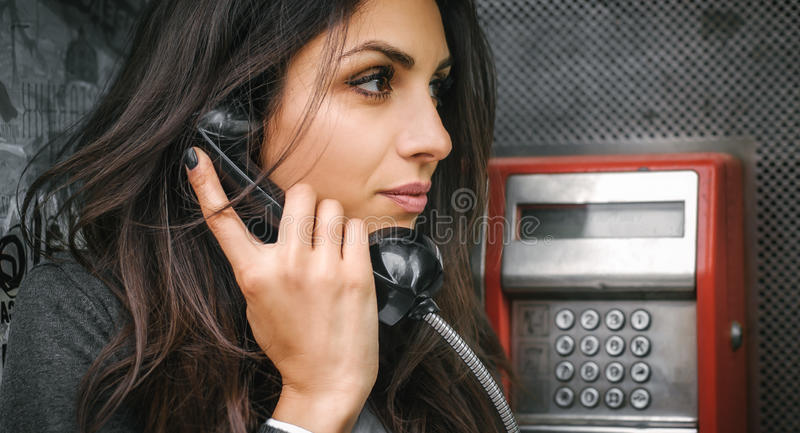 Fashion woman talking in the retro phone booth stock images
