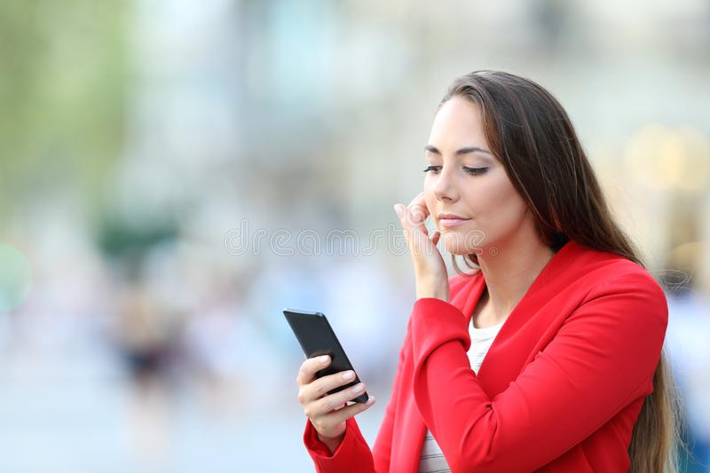 Fashion woman using phone as a mirror to comb her hair stock images