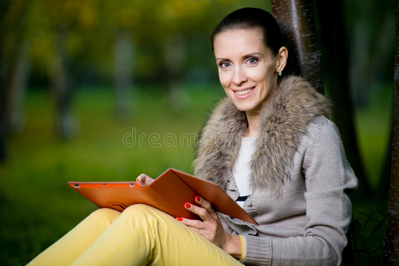 Fashion woman using a tablet computer outside in evening park stock images