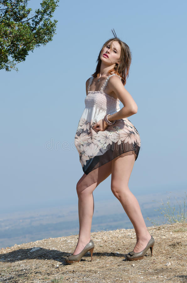 Fashion woman wear dress pose at the edge of a hill stock images