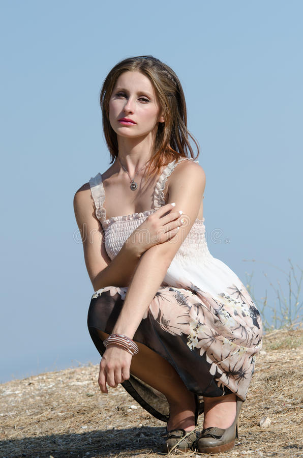 Fashion woman wear dress pose at the edge of a hill stock photography