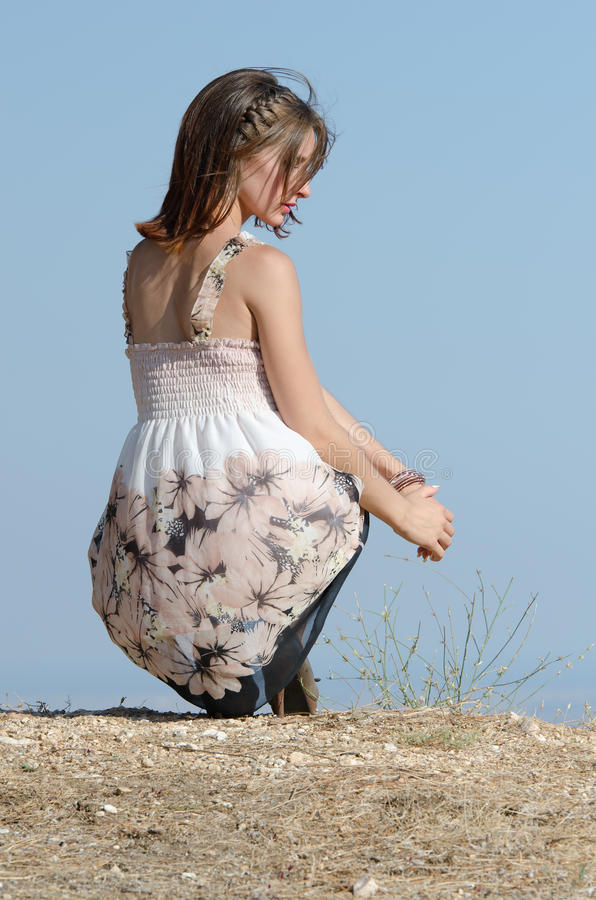 Fashion woman wear dress pose at the edge of a hill royalty free stock photography