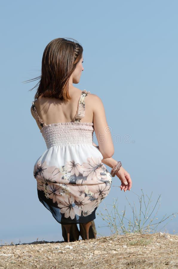 Fashion woman wear dress pose at the edge of a hill royalty free stock image