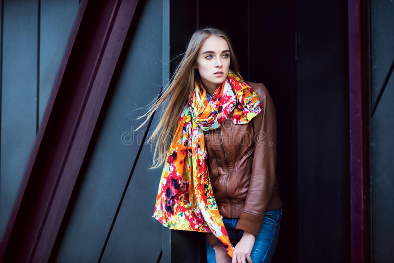 Fashion woman wearing leather coat and scarf posing against modern wall stock photos
