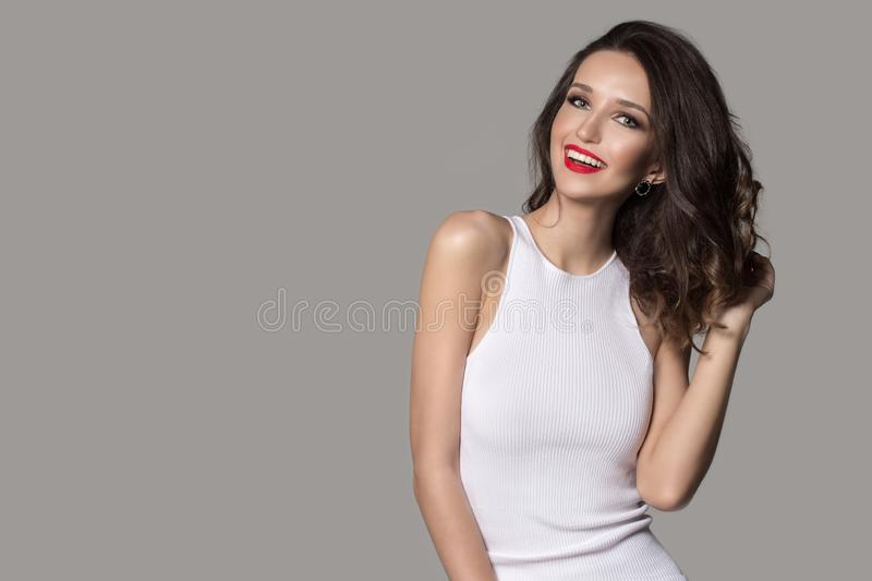 Fashion woman in white dress laughs. Red lipstick and beautiful makeup royalty free stock images