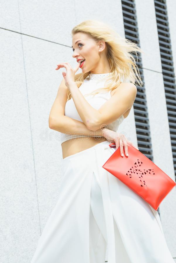 Fashion woman white outfit with red handbag. Attractive fashionable woman in trendy urban outfit white crop top trousers culottes posing outdoor. Female model royalty free stock image