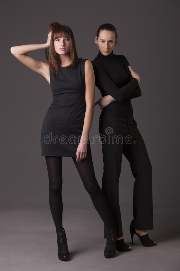 Fashion women in black. Two fashion women in black dresses and high heels showing new collection stock image