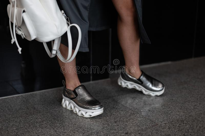Fashion women clothes. Stylish women`s shoes. Casual design. Close-up of female legs in silver leather sneakers. Street style. stock photography