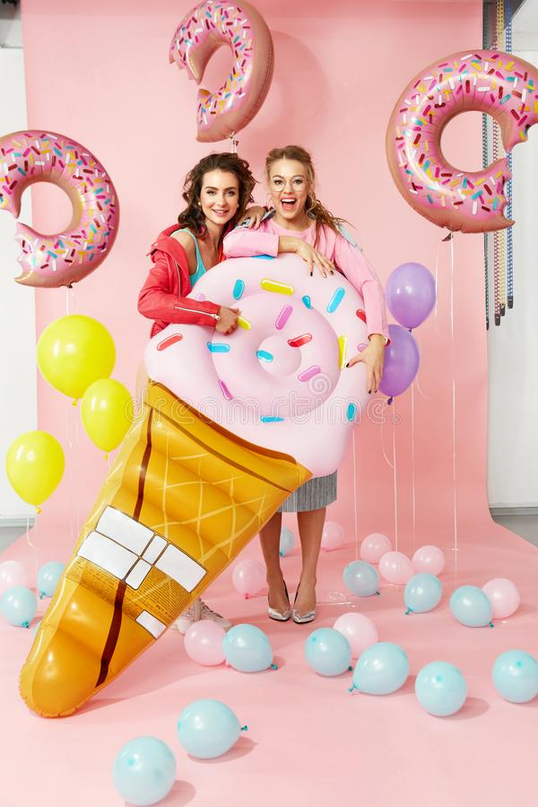 Fashion Women. Happy Friends In Summer Clothes. Beautiful Smiling Girls In Stylish Wear Having Fun And Laughing, Holding Big Inflatable Ice Cream On Colorful royalty free stock photography