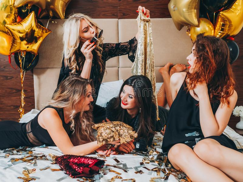 Fashion women relaxation sequin outfit confetti. Fashion women relaxation. Young females in black lying on bed choosing sequin outfit. Festive confetti and royalty free stock photos
