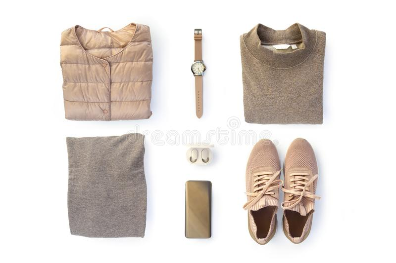 Fashion women`s clothes and trendy accessories set on white background. Stylish casual outfit. Vanilla pastel colors. Flat lay, stock photo