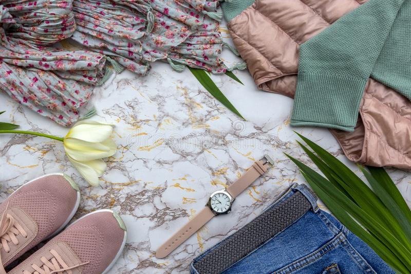Fashion women& x27;s clothes, tropical leaves trendy accessories set on beige white marble background. Stylish casual outfit. stock images