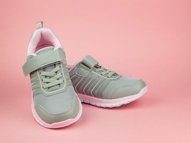 Fashion women`s sneakers gray and pink on a pink background. Sports shoes royalty free stock photos