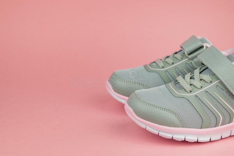 Fashion women`s sneakers gray and pink on a pastel background. Sports shoes royalty free stock images