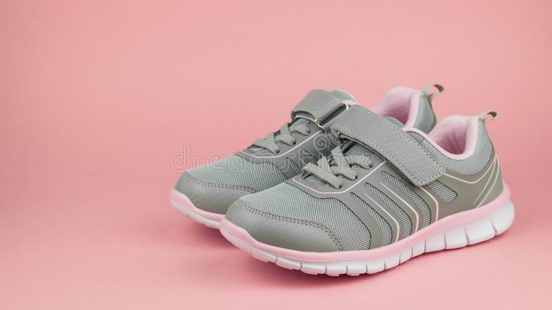 Fashion women`s sneakers gray and pink on a pastel pink background. Color trend. Fashion women`s sneakers gray and pink on a pastel pink background. Sports stock image