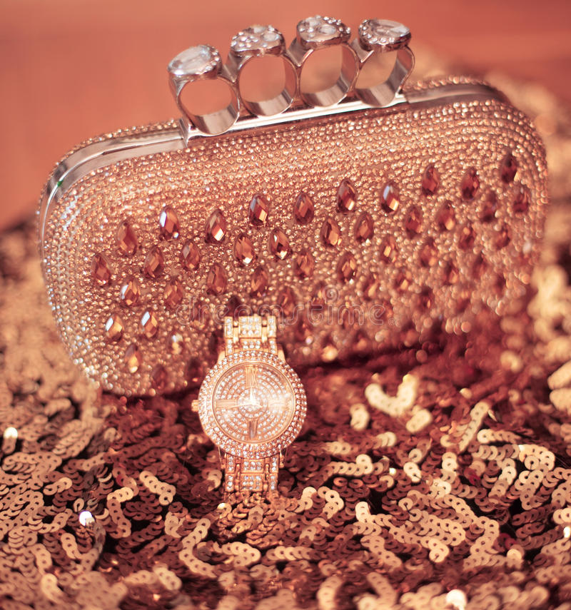 Fashion womens accessories. Luxury wristwatch and purse with strass and gems, on sequins sparkling sequined textile. Rich set cl. Oseup stock image
