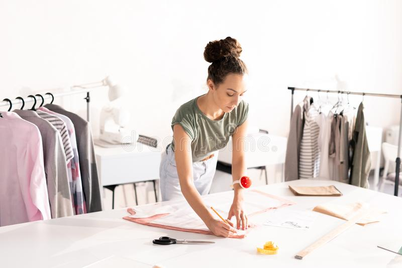 Fashion worker. Young seamstress outlining paper pattern pinned up to piece of textile while standing by desk in studio royalty free stock images