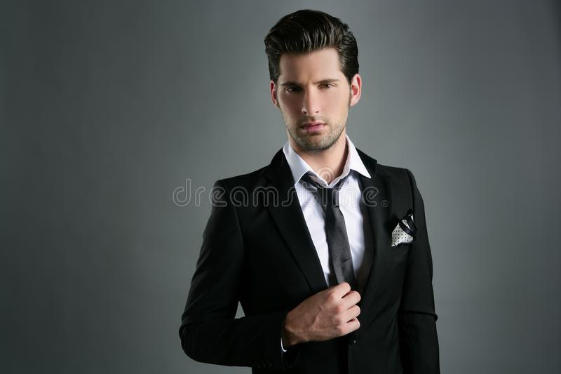 Fashion young businessman black suit casual tie stock photography