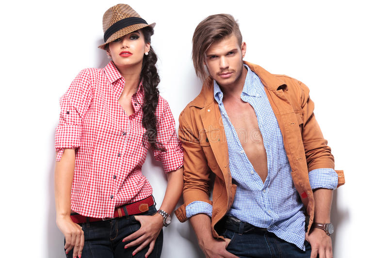Fashion young couple posing with hands in pockets royalty free stock photos